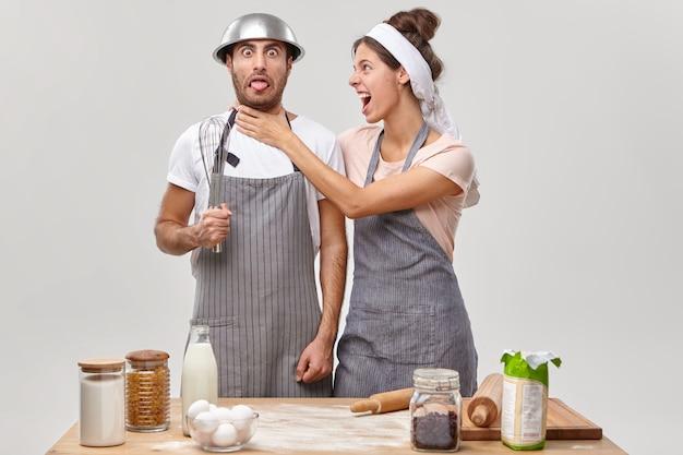 Boze vrouw houdt handen op de nek van echtgenoten, geïrriteerd door onervaren chef-kok op keuken, samen iets lekkers bereiden. grappige man met kom op hoofd en garde in de hand draagt een schort, leert koken