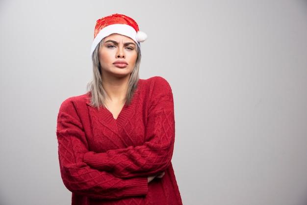 Boze vrouw in kerstmuts op zoek naar haar kant.