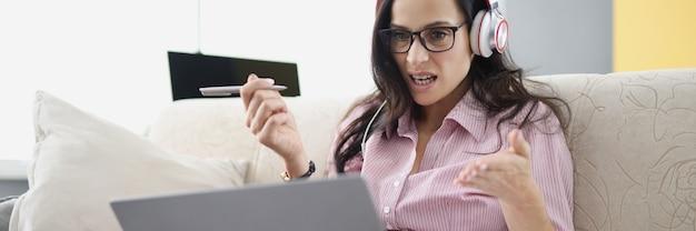 Boze vrouw met een bril en koptelefoon die voor een laptopmonitor zit met documenten thuis