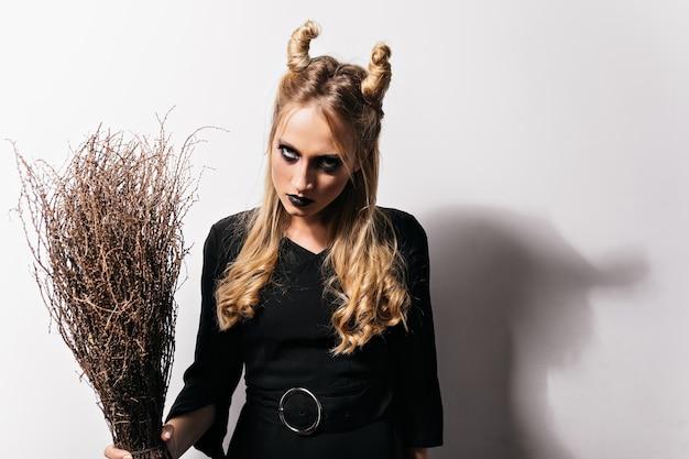 Boze vrouw met zwarte make-up carnaval voorbereiden. nadenkend blond meisje met grappig kapsel poseren in halloween kostuum.