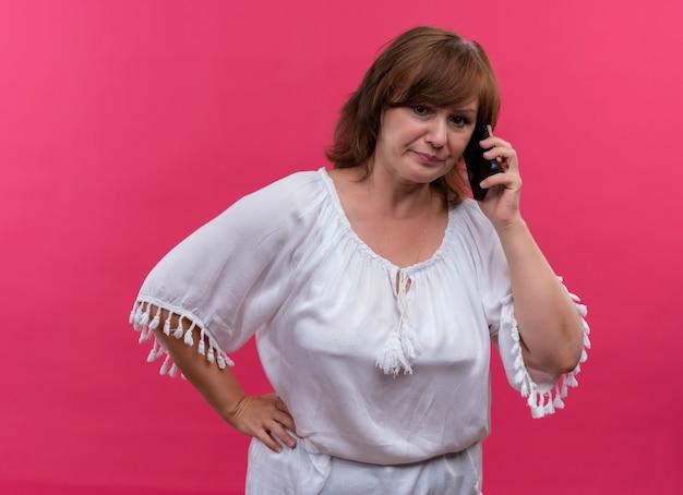 Boze vrouw van middelbare leeftijd die op telefoon spreekt en haar hand op taille op geïsoleerde roze muur legt