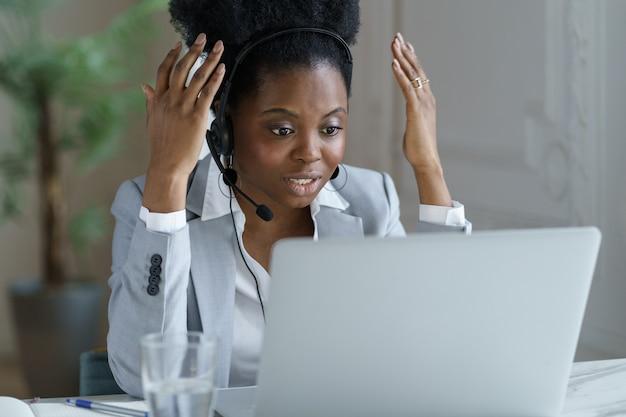 Boze vrouw werknemer in koptelefoon microfoon praten met klant in callcenter kantoor met frustratie