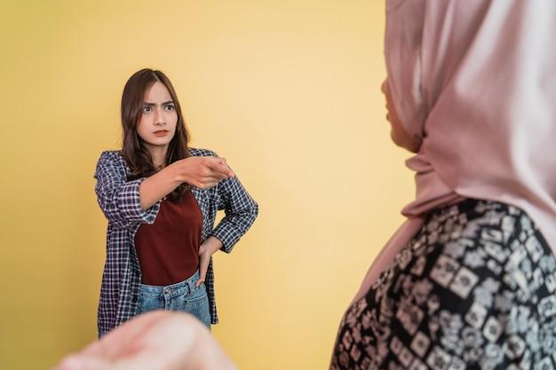 Boze vrouw wijzende vinger naar moslimvrouw in hijab met ontwijkend handgebaar