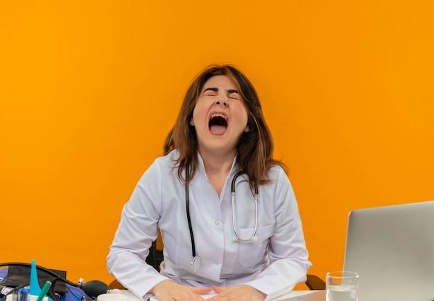 Boze vrouwelijke arts van middelbare leeftijd die medische mantel met stethoscoop zittend aan bureau werkt op laptop met medische hulpmiddelen op geïsoleerde oranje muur met kopie ruimte