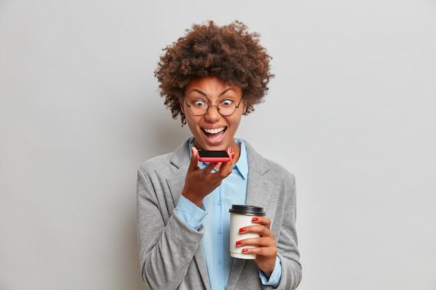 Boze vrouwelijke baas in grijze formele outfit, heeft spraakoproep, schreeuwt boos tegen collega die mislukt in bedrijfsrapport, drinkt afhaalkoffie, brengt tijd door op kantoor