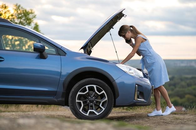 Boze vrouwelijke chauffeur die boos op mobiele telefoon spreekt met assistentiedienstmedewerker assistance