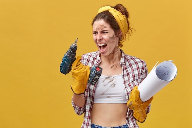 Boze vrouwelijke fabrieksarbeider die opgerold papier en boor vasthoudt en ernaar kijkt en schreeuwt woedend vanwege de storing van haar instrument. emotionele werkneemster met problemen tijdens het werk