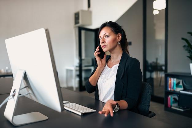 Boze vrouwelijke manager die op de telefoon in het bureau spreekt.