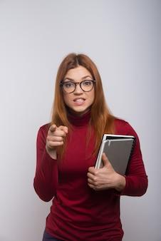Boze vrouwelijke student die met vinger richt