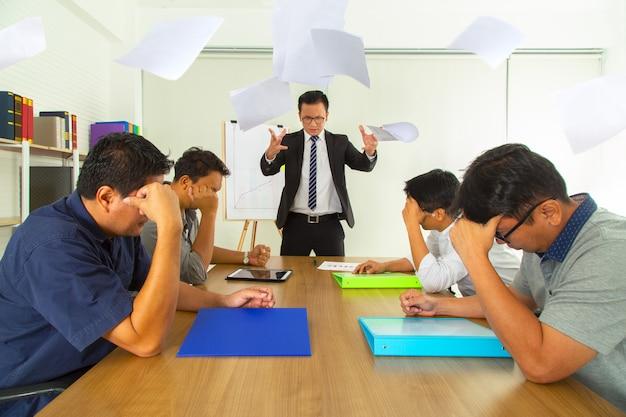 Boze werkgever ernstige het werpen van documenten ontevreden met slecht het werkresultaat. werknemer op zoek