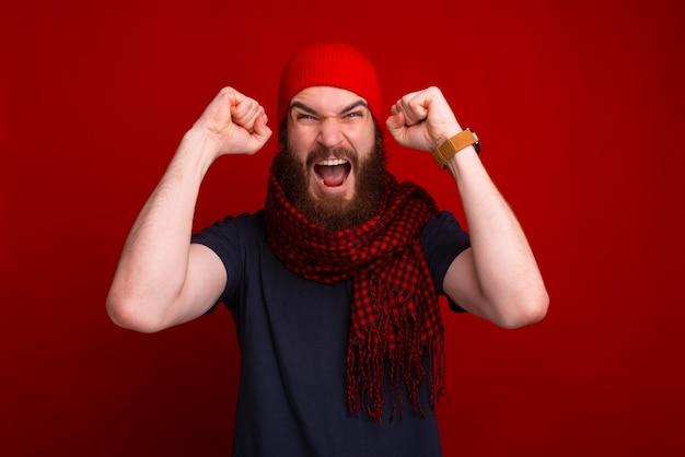 Boze winnaar, bebaarde man met warme kleren en vieren met armen omhoog en schreeuwen op camera