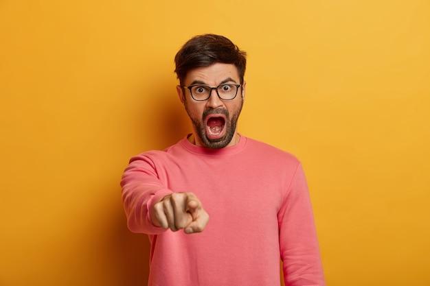 Boze woedende man geeft aan, geeft jou de schuld, schreeuwt van irritatie, zegt dat je schuldig bent, draagt een bril en een roze trui, poseert tegen gele muur, scheldt persoon uit voor het maken van een fout