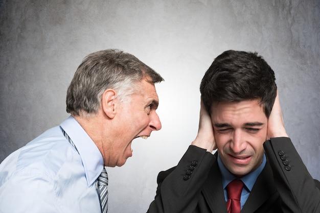 Boze zakenman die aan een werknemer schreeuwt