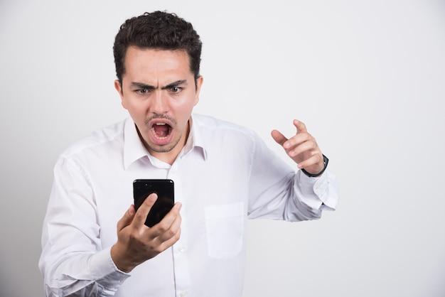 Boze zakenman die bij cellphone op witte achtergrond gilt.