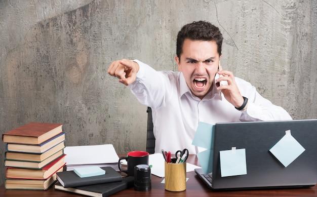 Boze zakenman die met telefoon bij het bureau spreekt.