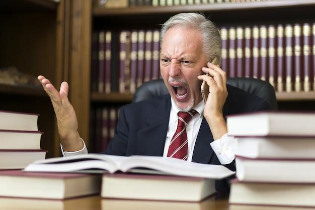 Boze zakenman die op cellphone schreeuwt terwijl het lezen van een boek