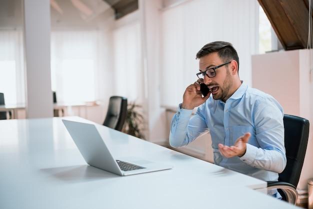 Boze zakenman die op de telefoon in bureau spreekt