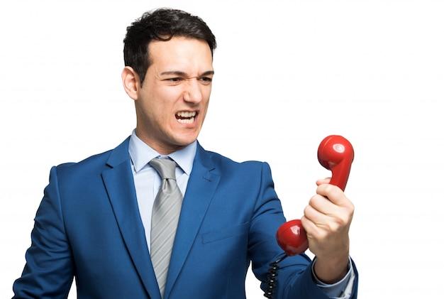 Boze zakenman die op de telefoon schreeuwt die op wit wordt geïsoleerd