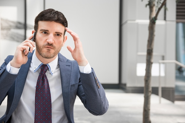 Boze zakenman die op smartphone spreekt