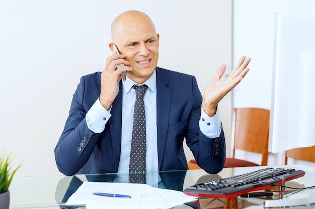 Boze zakenman witte kraag werknemer klassieke pak achter bureau zitten en schreeuwen op smartphone dragen