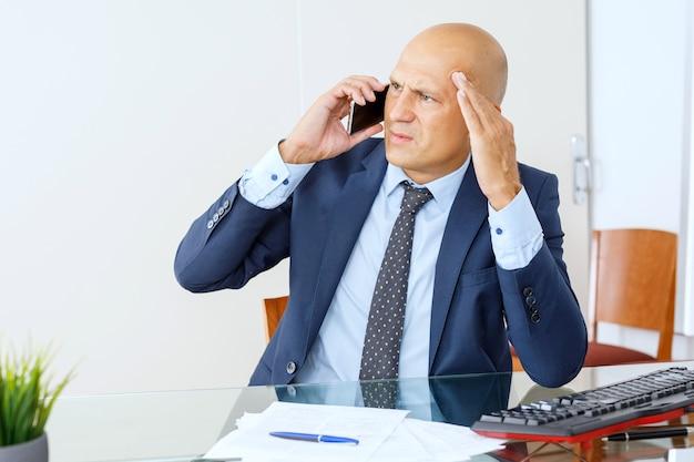 Boze zakenman witte kraag werknemer klassieke pak zittend op kantoor dragen