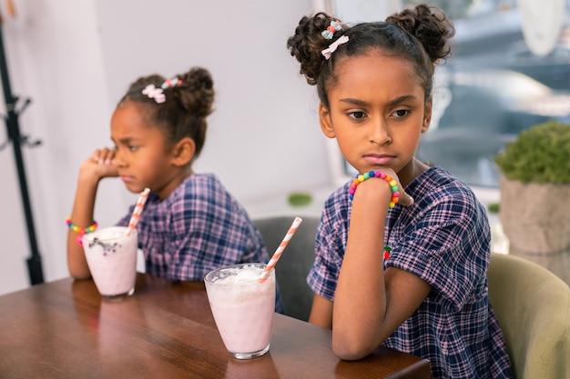 Boze zus. krullende zus met donkere ogen die boos is na ruzie met haar kleine zusje na het delen van speelgoed