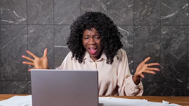 Boze zwarte zakenvrouw met krullend haar schreeuwt naar bedrijfsmedewerkers tijdens online conferentie zittend aan bruine houten tafel met laptop