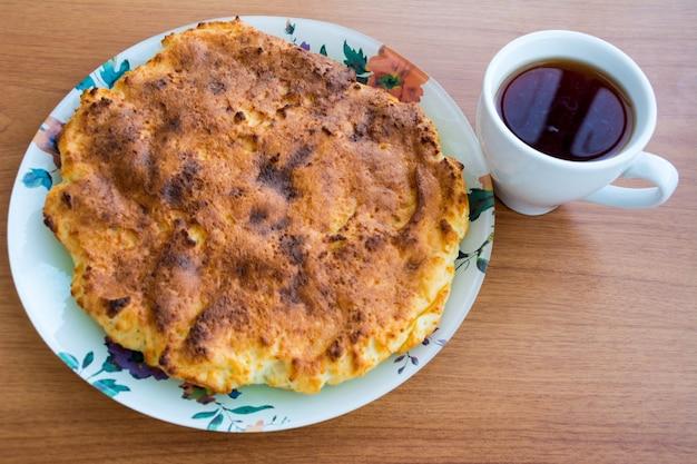 Braadpan op een bord met een kopje thee op de houten tafel. eigengemaakt
