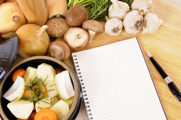 Braadpan pot met biologische groenten en kruiden op keuken aanrecht met leeg kookboek of receptenboek