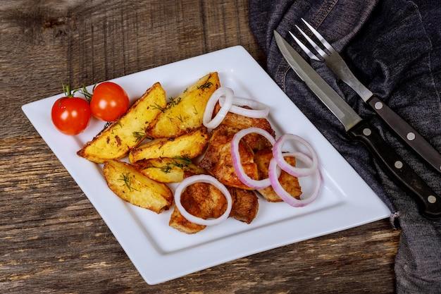 Braadstukvarkensvlees op ui en aardappels op witte plaat