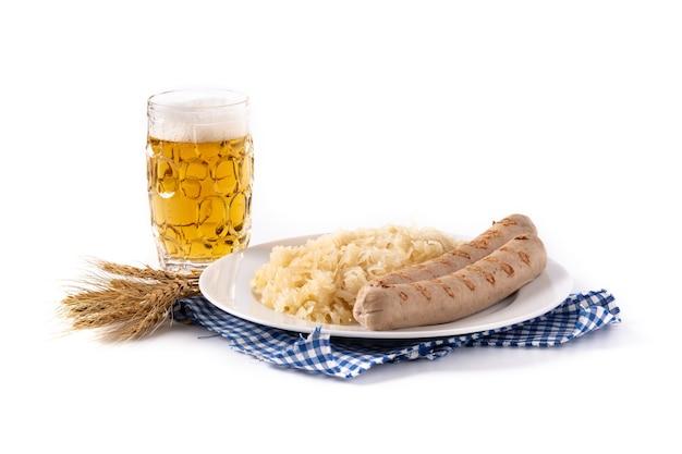 Braadworstworst, zuurkool, pretzels en bier dat op witte achtergrond wordt geïsoleerd
