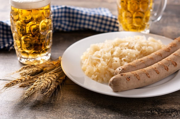 Braadworstworst, zuurkool, pretzels en bier op houten tafel
