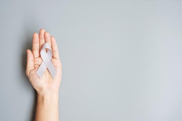 Brain cancer awareness month, vrouwenhand met grijs kleurenlint voor het ondersteunen van mensen die leven. gezondheidszorg en wereldkankerdag concept