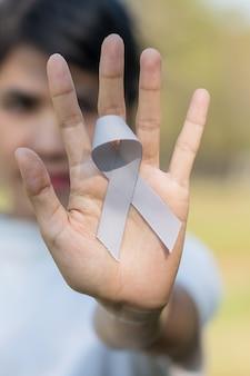 Brain cancer awareness month, vrouwenhand met grijs kleurenlint voor het ondersteunen van mensen die leven.