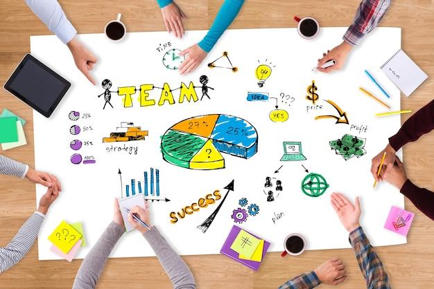 Brainstorm. bovenaanzicht close-up beeld van mensen die aan de houten tafel zitten met kleurrijke schetsen erop