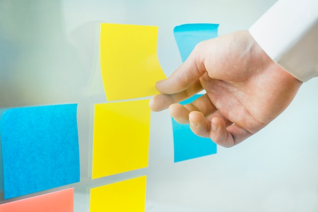 Brainstorm. de mannelijke hand lijmt multi-coloured kleverige nota's op een raad - beeld. zakelijke notities.