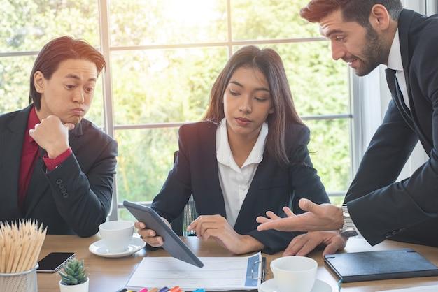Brainstorm met multi-etnische collega's uit het bedrijfsleven. aziatische zakenvrouw houdt tablet met haar zakelijke team in het kantoor.