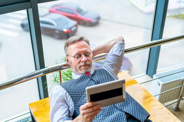 Brainstormen. man aan tafel met tablet in handen. ideeën zoeken op internet. het concept van zaken, computerwerk, freelance werk op afstand.