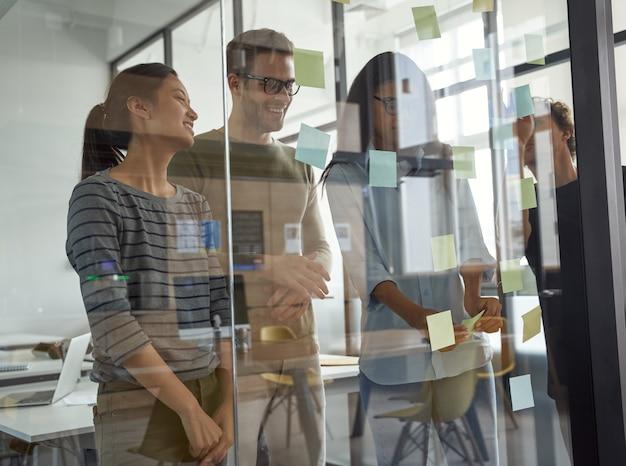 Brainstorming concept groep gelukkige creatieve zakenmensen kijken naar plaknotities op glas