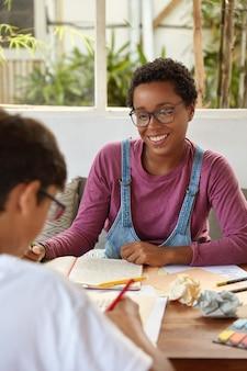Brainstroming en onderwijsconcept. twee studenten bespreken hun onderwerp, schrijven in een notitieblok, maken een artikel voor blog, bespreken ideeën voor ontwikkeling, zitten in een coworking-ruimte. tutor geeft privéles