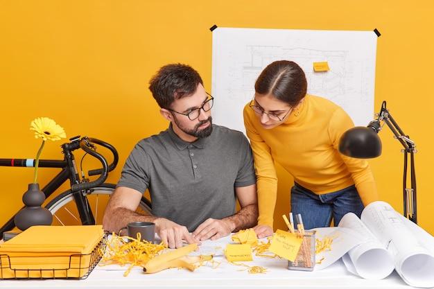 Brainstroming vergader- en samenwerkingsconcept. attente studiecursussen voor vrouwen en mannen in modern kantoorinterieur werk aan gemeenschappelijke ontwerpprojecthouding op desktop hebben gerichte uitdrukkingen op kranten