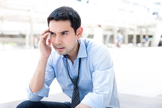 Brak werkloze gestresste aziatische zakenmanzitting in openlucht
