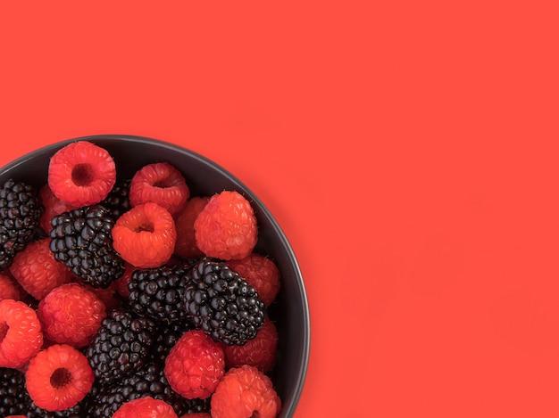 Bramen en frambozen in een zwarte kom. rode achtergrond. bovenaanzicht.