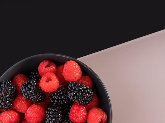 Bramen en frambozen in een zwarte kom. zwart en licht roze achtergrond.