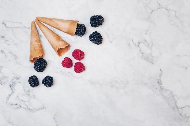 Bramen en frambozen in wafel ijsje op witte marmeren achtergrond. zomer voedselconcept. bovenaanzicht.