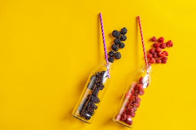 Bramen en frambozenvruchten in glazen flessen met rietjes