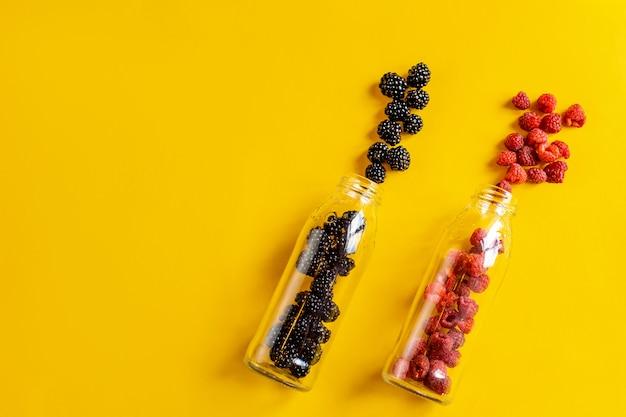 Bramen en frambozenvruchten in glazen flessen