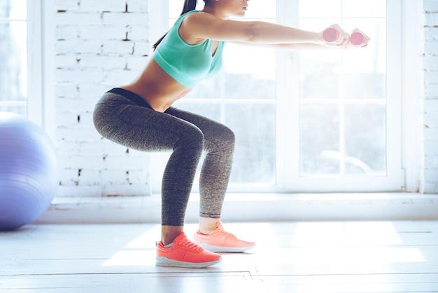 Brand in de billen. zijaanzicht van een jonge vrouw in sportkleding die squat doet en halters vasthoudt terwijl ze voor het raam in de sportschool staat