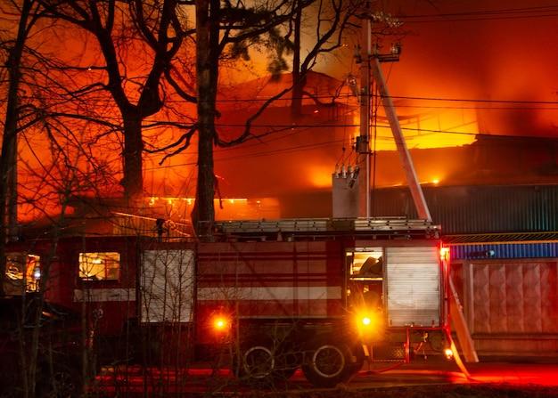 Brand in het fabrieksgebouw 's nachts. brandweerlieden proberen het vuur te blussen
