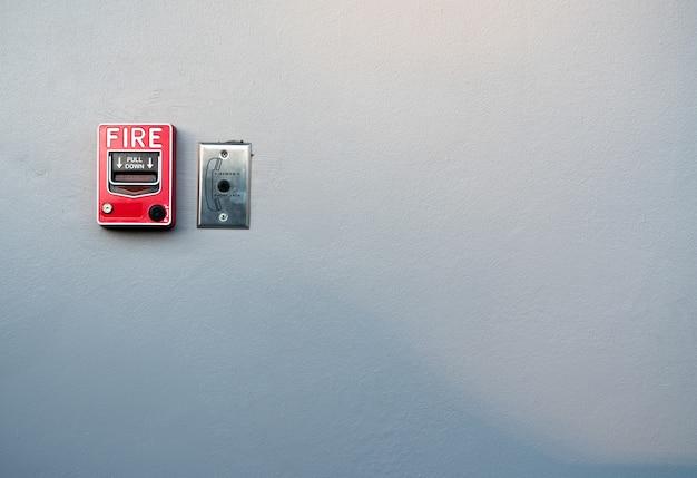 Brandalarm op witte betonnen muur. waarschuwings- en beveiligingssysteem. noodapparatuur voor veiligheidswaarschuwing. rode doos met brandalarm.